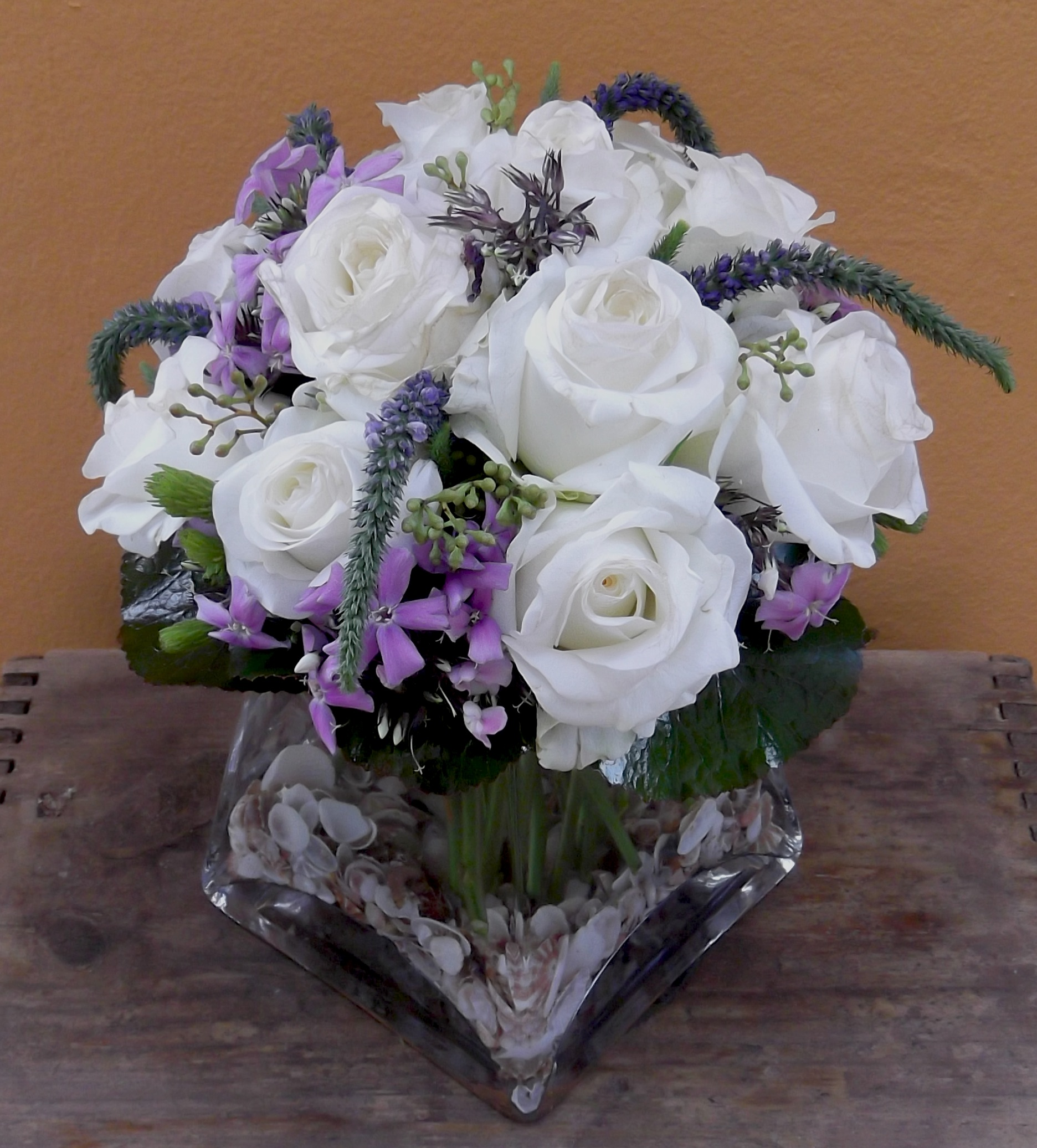 A dozen white roses 60 fusion floral art small shells in the glass vase blue purple flowers add a beachy touch to a dozen white roses 60 mightylinksfo