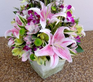 Delicate mix of seasonal blooms in shades of pink, yellow & puple set a soft tone for the evening. Price - $75