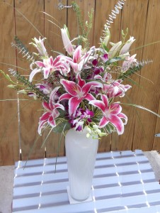 """Spectacular Stargazer lillies mingle with purple dendrobium orchids and branches of silver eucauliptus in this 16"""" tall white glass vessel. Approx. 3' H."""