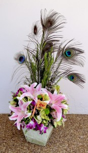 Peacock feathers stand proud amidst fragrant pink lillies, purple dendrobium orchids, yellow & pink astromeria blooms. Approx. 2' High. Price: $95